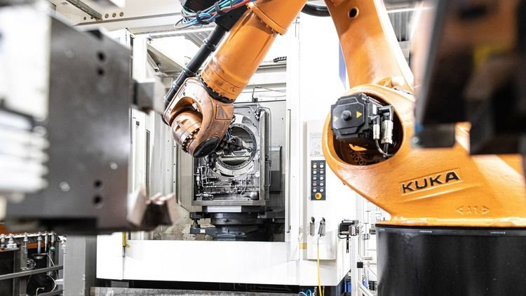 As soon as the machining process has been completed in the machine, the robot deburrs the part at the changeover station. © Kuka